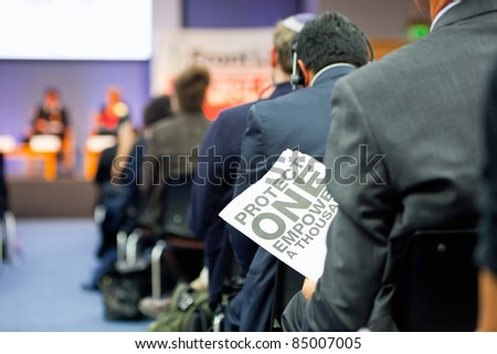 man  holding a poster with sign 'Protect One Empower a Thousands' during presentation in busy  auditorium