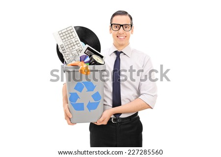 Man holding a recycle bin with bunch of old stuff isolated on white background - stock photo
