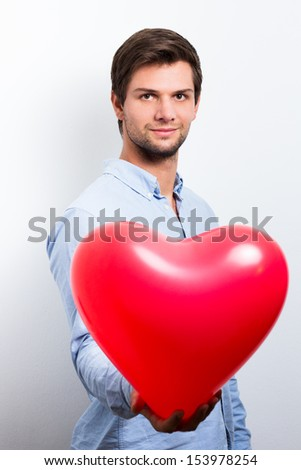 Man holding a red heart balloon