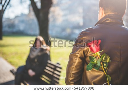 Man holding a red rose behind back, woman siting on the park bench in the background
