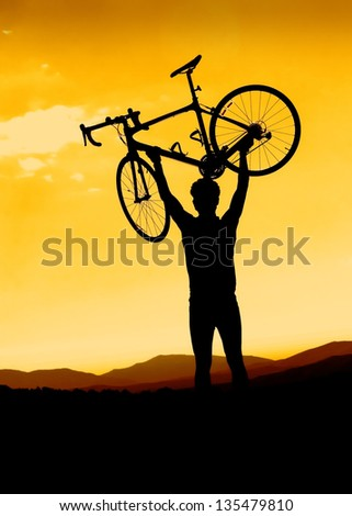 Man holding a road bike over his head with sunset background - stock photo