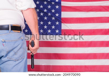 Man holding a semi-auto pistol in front of an American flag - stock photo