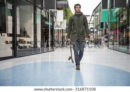 Man, holding a skateboard, strolling casually past the shops at a shopping mall - stock photo