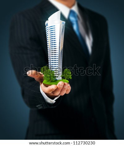 Man holding a skyscraper  in hand