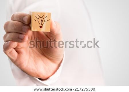 Man holding a small wooden cube with a hand-drawn illuminated light bulb conceptual of inspiration, imagination and innovation, with copyspace. - stock photo