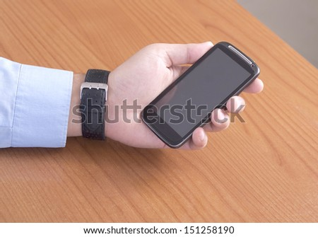 Man holding a Smart Phone on the Desk