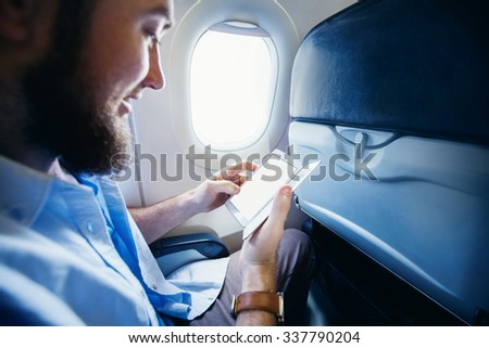Man holding a smart phone with blank screen in airplane. Template for a travel app design, blank screen - stock photo