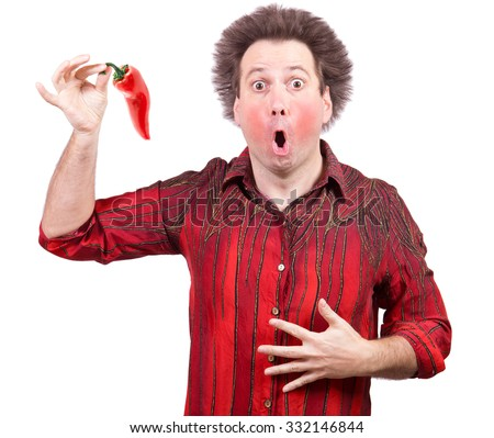 Man holding a spicy red paprika isolated on white background. The shock of hot chili peppers. Red face from eating hot vegetable.
