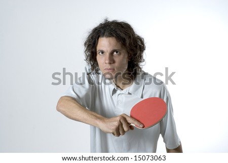 Man holding a table tennis paddle wears a serious expression on his face. Horizontally framed photograph.
