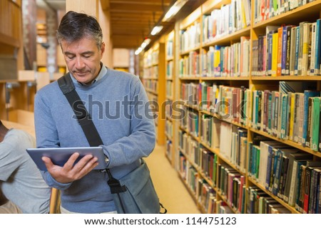 Man holding a tablet pc amongst shelves in a library