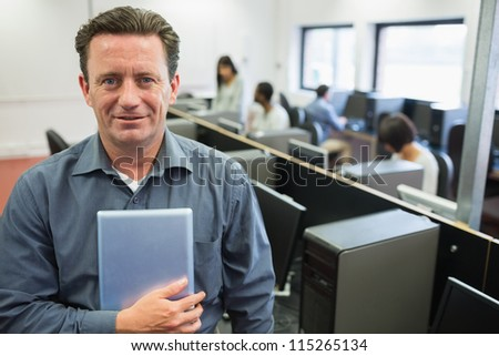 Man holding a tablet pc in computer room and smiling - stock photo