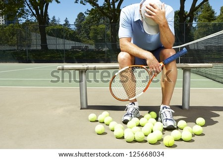 man, holding a tennis racquet, sitting on a bench holding his head down, tennis balls in front of him, tennis net visibile on his right side, trees in the background - stock photo