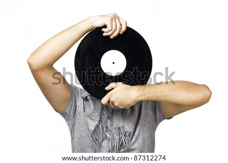 man holding a vinyl disk in front of his head - stock photo
