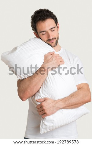 Man holding a white pillow, isolated in a light background - stock photo
