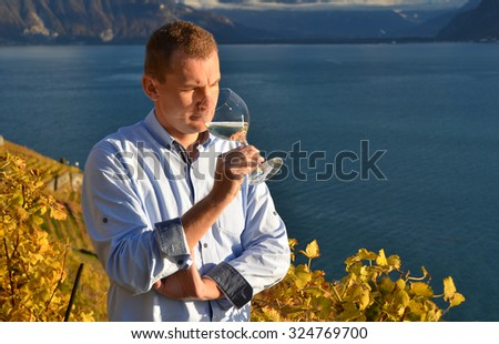 Man holding a wineglass against wineyards in Lavaux, Switzerland - stock photo