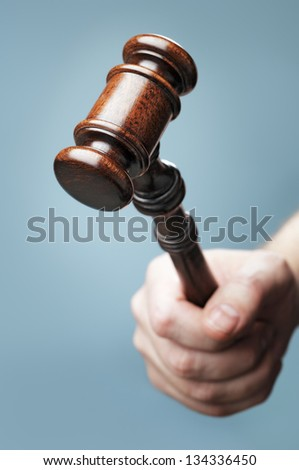 Man holding a wooden mahogany gavel in his hand. Short depth-of-field. - stock photo