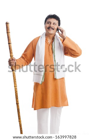 Man holding a wooden staff and talking on a mobile phone - stock photo