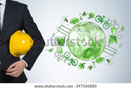 man holding a yellow helmet, a green picture of eco energy icons arranged in circle, earth in the centre to the right of him, concept of clean and safe  environment, breast view - stock photo
