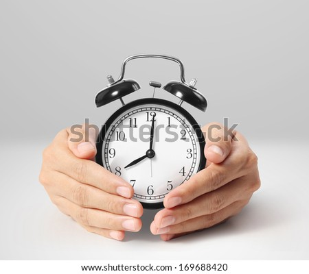 man holding alarm clock in the hands