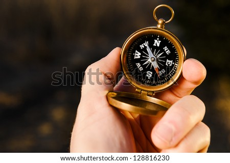 man holding an antique compass to find direction