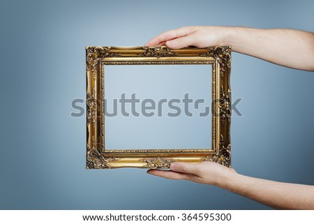 Man holding an antique style golden frame in his hands. - stock photo