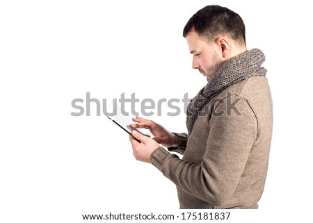 Man holding an electronic writing tablet. Young businessman working on his electronic tablet. Realtor and insurance records data in email client address book. Man looks, reads in pad. Space for text.