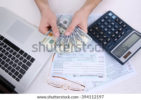 Man holding and counting money at the table