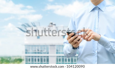 Man holding and touching on mobile phone with blurred building on background. - stock photo