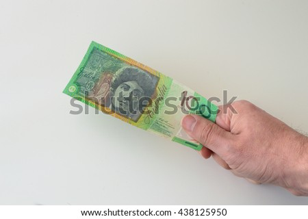 Man holding Australian Dollar banknote in his hands