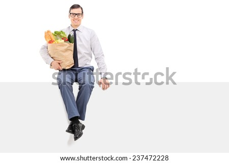 Man holding bag of groceries seated on panel isolated on white background - stock photo