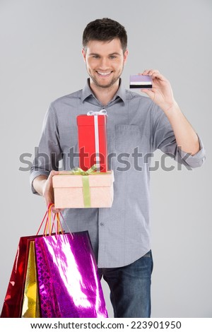 man holding bagsand boxes with credit debit card. young happy excited guy holding credit card on grey - stock photo