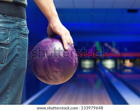 Man holding ball against bowling alley - stock photo