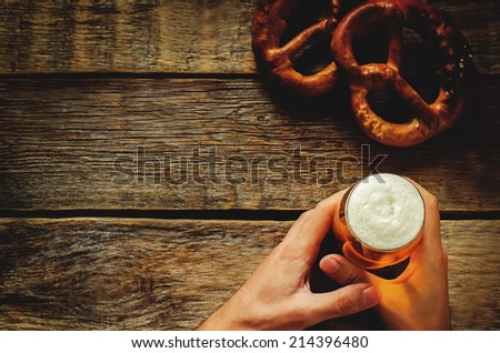 man holding beer on a dark wood background. tinting. selective focus on the foam in the glass - stock photo