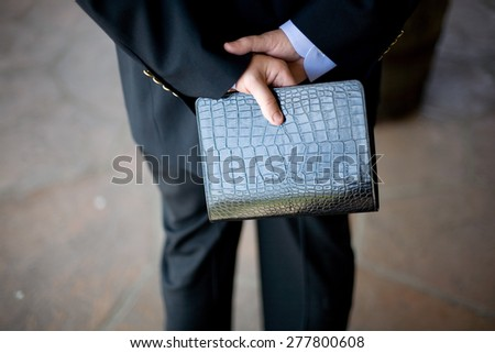 Man holding Bible behind his back - stock photo