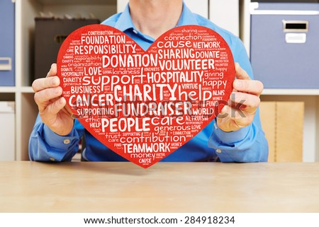 Man holding big red heart with charity and fundraiser tag cloud against cancer - stock photo