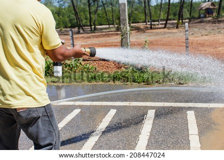 Man holding big water hose to clean the road - stock photo