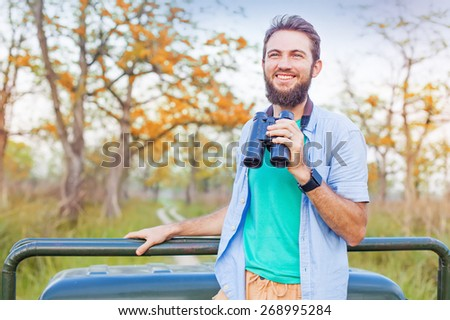 man holding binocular in a safari ride in national park - stock photo
