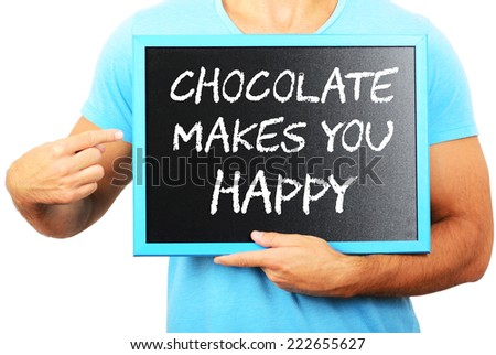 Man holding blackboard in hands and pointing the word CHOCOLATE MAKES YOU HAPPY