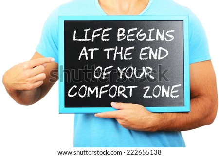 Man holding blackboard in hands and pointing the word LIFE BEGINS AT THE END OF YOUR COMFORT ZONE