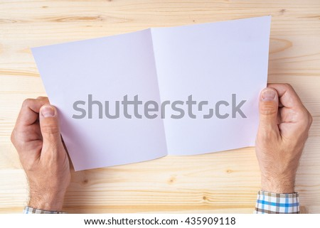 Man holding blank brochure as mock up copy space for graphic design or text placement - stock photo