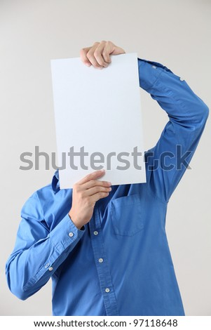 Man holding blank paper cover the face - stock photo
