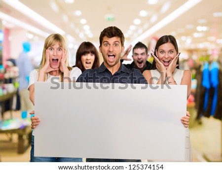 Man Holding Blank Placard And Woman Screaming From Behind, Indoor - stock photo