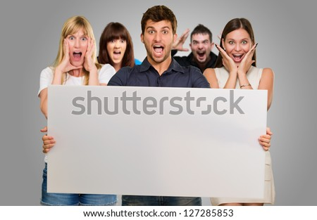 Man Holding Blank Placard And Woman Screaming From Behind On Gray Background