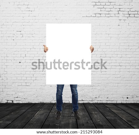 man holding blank placard in brick room - stock photo
