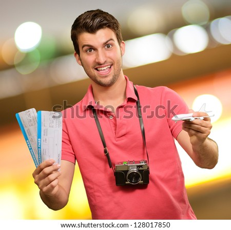 Man holding boarding pass and airplane, outdoor