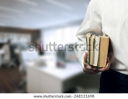 Man holding books on blurred office background. Finding a job, looking for a job concept. - stock photo
