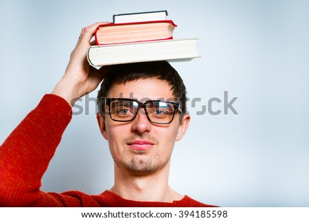 man holding books on her head, isolated on a gray background