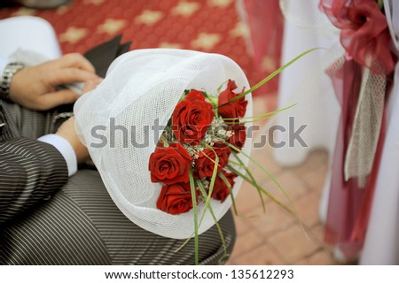 man holding bouquet of red roses