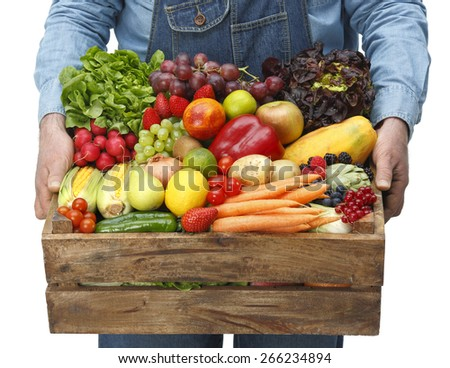 Man holding box full of fresh fruits and vegetables - stock photo