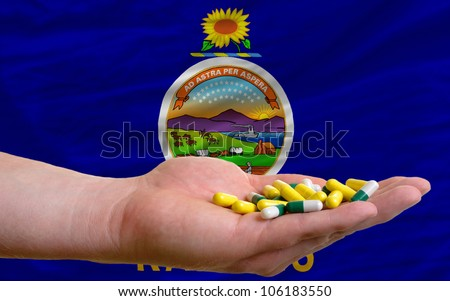 man holding capsules in front of complete wavy american state flag of kansas symbolizing health, medicine, cure, vitamins and healthy life - stock photo
